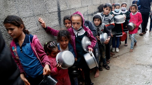 Palestinian children wait in line to receive free meals in Gaza City.