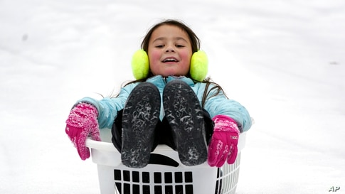Peyton McKinney uses a laundry basket for a sled in Nolensville, Tennessee, Feb. 15, 2021. Much of Tennessee was hit with a winter storm that brought freezing rain, snow, sleet and freezing temperatures.