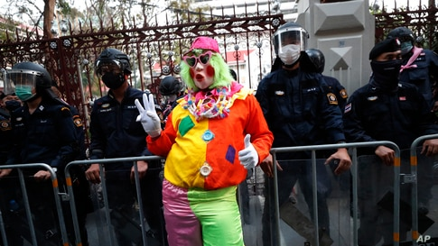 A pro-democracy protester wearing a clown costume raises a three-finger salute in front of riot police at Police Headquarter in Bangkok, Thailand.Protesters gathered to call for fairness for low-ranking police.