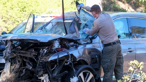 A law enforcement officer inspects a damaged vehicle following a rollover accident involving golfer Tiger Woods, Feb. 23, 2021, in the Rancho Palos Verdes suburb of Los Angeles, California.