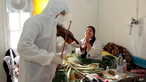 Dr. Mohamed Salah Siala plays the violin for patients in the COVID wards of the Hedi Chaker hospital in Sfax, eastern Tunisia, Feb. 20, 2021.