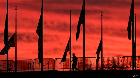 A runner passes under the flags hanging at half-staff surrounding the Washington Monument at day break in Washington, D.C.