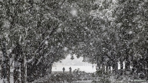 People make their way at the Zappeion area during heavy snowfall in Athens, Greece.