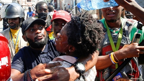Journalists help a colleague who fainted after police threw tear gas during a protest against Haiti's President Jovenel Moise, in Port-au-Prince, Feb. 10, 2021.