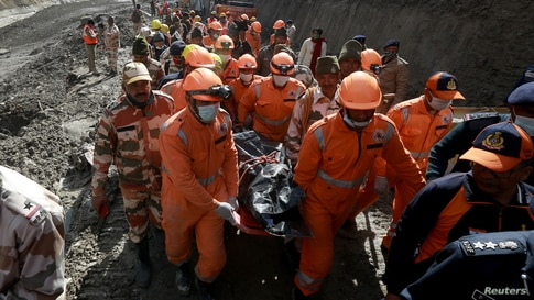 Members of National Disaster Response Force (NDRF) carry the body of a victim after recovering it from the debris during a rescue operation outside a tunnel after a part of a glacier broke away, in Tapovan in the northern state of Uttarakhand, India.