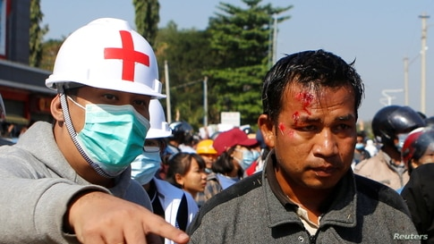 An injured protester is seen next to medical personnel, as protesters rally against the military coup and to demand the release of elected leader Aung San Suu Kyi in Naypyitaw, Myanmar, Feb. 9, 2021.