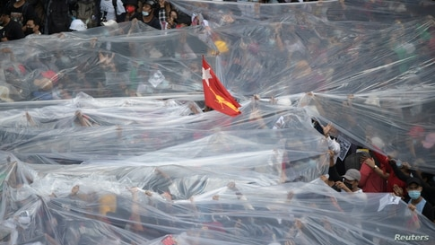 People cover under plastic sheets in case of a water canon during a rally against the military coup and to demand the release of elected leader Aung San Suu Kyi, in Yangon, Myanmar, Feb. 9, 2021.