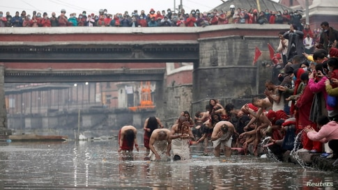 Devotees take a holy bath at Bagmati River in Pashupatinath Temple during the Swasthani Brata Katha festival in Kathmandu, Nepal.