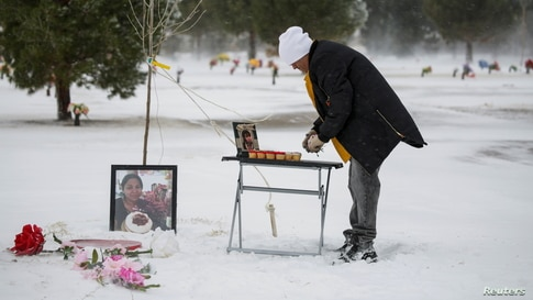 Antonio Cervantes brings gifts to the grave of his wife Gabriela, who died of the coronavirus disease (COVID-19), for Valentine's Day, at a cemetery in Santa Teresa, New Mexico, Feb. 14, 2021.
