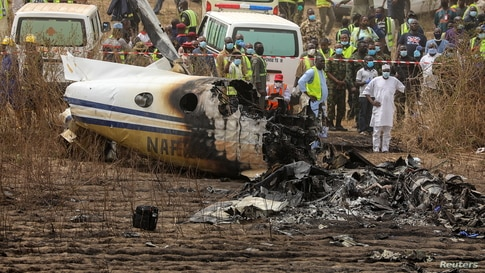 Rescuers and people gather near the debris of a Nigerian air force plane, which crashed while approaching the Abuja airport runway in Abuja.