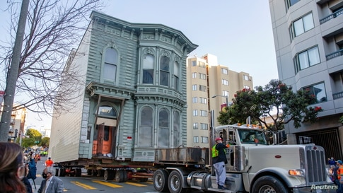 Workers move a 139-year-old Victorian house known as the Englander House to a new location in San Francisco, California, Feb. 21, 2021. A 48-unit, eight-story apartment building will be built at the original site.
