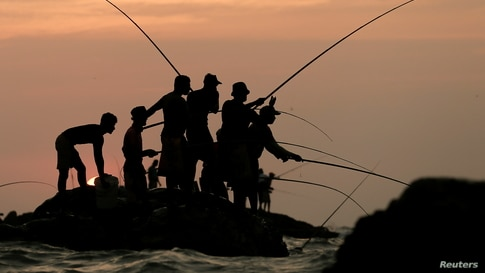 Men fish on top of a rock in the sea in Colombo, Sri Lanka.