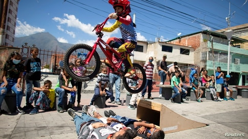 Camila Iachini, 8, performs with her bike during celebrations for the 400th anniversary of the founding of the neighbourhood Petare, in Caracas, Venezuela, Feb. 17, 2021.