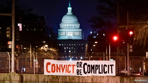 "A banner reading, ""Convict or be complicit"" is hung over a bridge on the first day of the Senate impeachment trial against former President Donald Trump in Washington, D.C., Feb. 9, 2021."