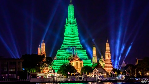 The stupa of the Buddhist temple Wat Arun (Temple of Dawn) is illuminated in green to mark St. Patrick's Day in Bangkok on…