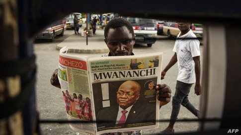 A man reads a newspaper with a headline announcing the death of Tanzania's President John Magufuli in Dar es Salaam, on March…