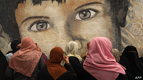 Palestinian women take part in a protest against the cuts in food aid distribution, outside the United Nations Relief and Works…