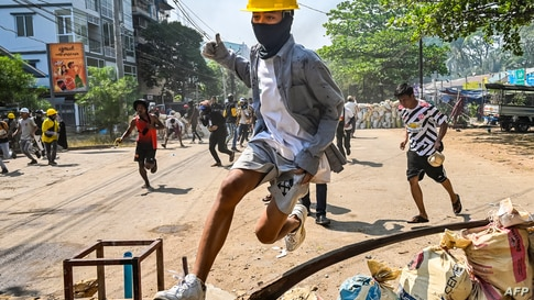 A protester jumps over a makeshift barricade during a crackdown by security forces on a demonstration against the military coup…
