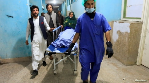 Afghan men transport the body of one of three female media workers who were shot and killed by an unknown gunmen, at a hospital in Jalalabad, Afghanistan, March 2, 2021.