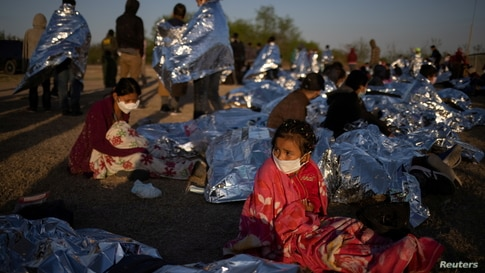 Hennessy, a four year old asylum-seeking migrant girl from Honduras, awakes at sunrise next to others who took refuge near a…