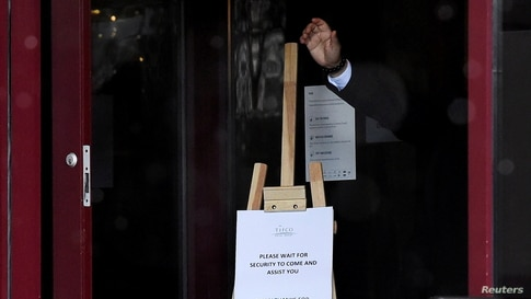 Hotel staff gestures at the entrance of Crowne Plaza Dublin Airport Hotel, as Ireland introduces hotel quarantine programme for…