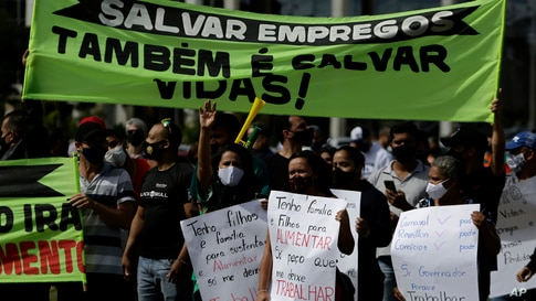 "Demonstrators hold Portuguese messages like ""Saving jobs is also saving lives"" outside a city government office to protest a two-week-long lockdown to curb the spread of COVID-19 in Brasilia, Brazil, March 1, 2021."