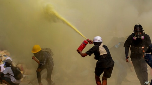 An anti-coup protester uses a fire extinguisher to provide cover for others as security forces approach their encampment in…