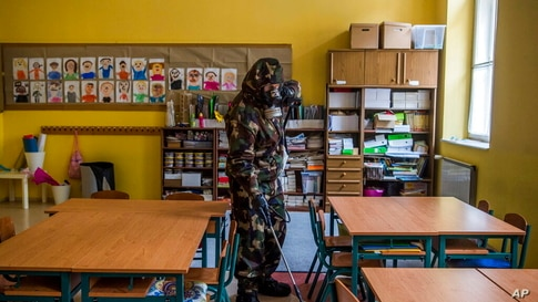A Hungarian soldier wearing a hazmat suit disinfects a classroom of a combined kindergarten and elementary school in an effort…