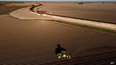 In this photo taken by a drone, the border wall construction is seen near farmland as a tractor plows a field