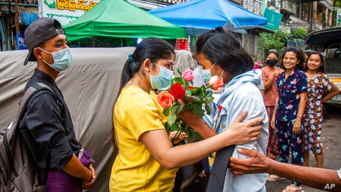 An anti-coup student protester is welcomed home with flowers by the residents of her neighborhood after being released from…
