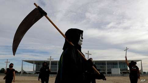 A demonstrator dressed as death performs outside Planalto presidential palace to protest the president's handling of the COVID…