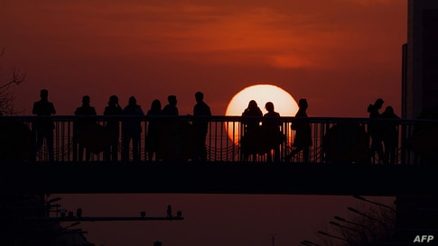 People watch the sunset at an overpass in Beijing, China.