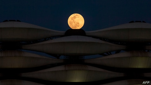 """A view of the rising full """"Worm Moon"""" above Basra International Stadium in the southern Iraqi city, March 28, 2021."""