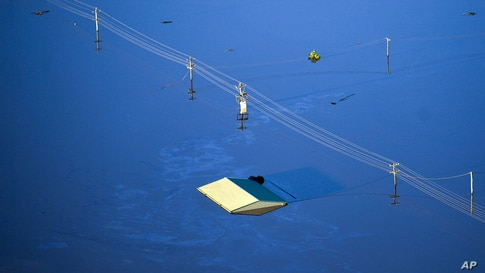 The roof of a structure is visible as floodwater covers large areas northwest of Sydney, Australia.