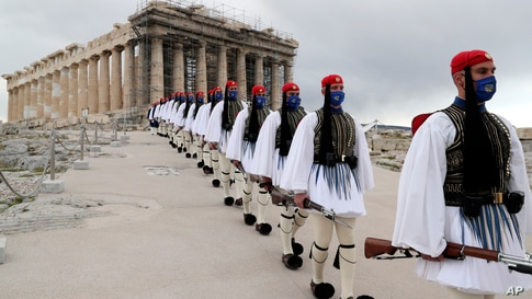Members of the Presidential Guard walk in front of the Parthenon temple atop of Acropolis Hill after the Greek flag raising ceremony in Athens.