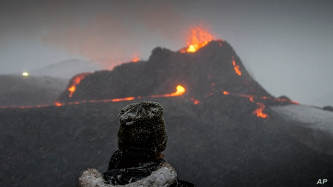 A person watches as lava flows from an eruption of a volcano on the Reykjanes Peninsula in southwestern Iceland, March 24, 2021.