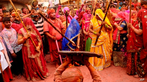 Indian women from Barsana village beat a villager from Nandgoan with wooden sticks as he teases them during Lathmar holi festival celebrations at the legendary hometown of Radha, consort of Hindu god Krishna, in Barsana.