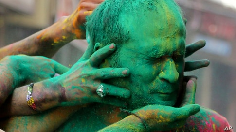 Indians smear colored powder on each other as they celebrate Holi in Jammu.