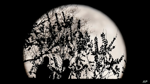 A couple are silhouetted against the rising full moon as they gather in a park, March 28, 2021, in Kansas City, Missouri.