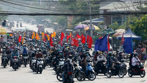Protesters carry flags as they drive their motorcycles during an anti-coup protest in Mandalay, Myanmar.