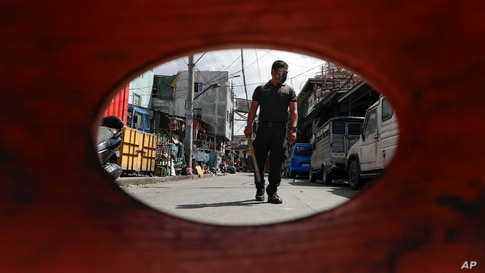 A policeman patrols inside a village under lockdown as the government implements stricter measures to prevent the spread of the coronavirus in Manila, Philippines.