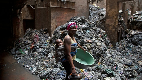 A woman with her child on her back walks past piles of rubbish in a building in Hillbrow, Johannesburg, South Africa.