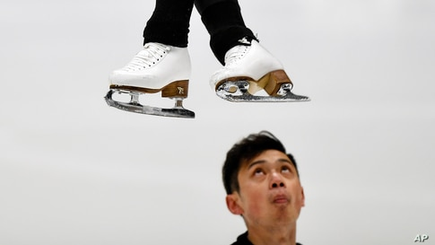 Yang Jin from China watches his partner Cheng Peng jumping during a practice session of the pairs at the Figure Skating World Championships in Stockholm, Sweden.