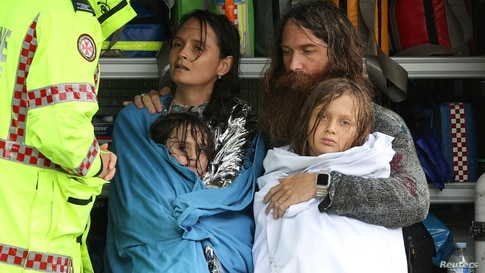 A family receives medical attention after being by the Marine Rescue boat as the state of New South Wales experiences widespread flooding and severe weather, in the suburb of Sackville North in Sydney, Australia.