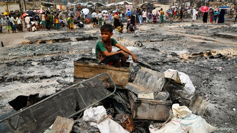 A Rohingya refugee boy sits on a stack of burned material after a massive fire broke out and destroyed thousands of shelters in a Rohingya refugee camp in Cox's Bazar, Bangladesh.