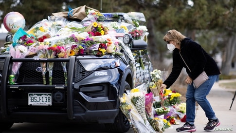 Karla Bielanski places flowers on the car of Officer Eric Talley, who was killed during a mass shooting in King Soopers grocery store, at Boulder Police Department, in Boulder, Colorado, March 23, 2021.