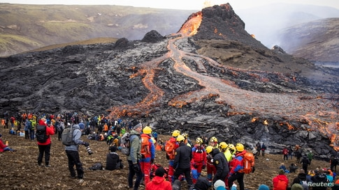People gather at the volcanic site on the Reykjanes Peninsula following Friday's eruption in Iceland, March 21, 2021.