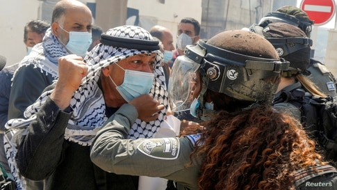 "A Palestinian demonstrator scuffles with an Israeli border policewoman during a protest marking ""Land Day"", in Sebastia near Nablus, in the Israeli-occupied West Bank."