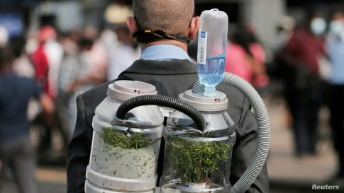A climate activist wears an oxygen mask to demonstrate the possibility of pumping oxygen from a tree in a bottle, during a protest against the government's deforestation practices of Sri Lanka's main wildlife forests for developments in Colombo.