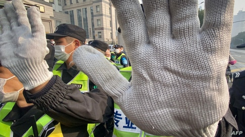 A policeman blocks the camera to stop journalists from recording footage outside the Shanghai Pudong New District People's…